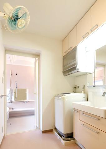 洗面化粧台を組み込んだ間口1m65cmのシステム収納の扉カラーは、奥さまのお好きなスフレピンクを選ばれました。 雑然としがちな小物や洗剤等をすっきり納められる洗濯機用シェイプアップキャビネットなど、使いやすさとインテリ>