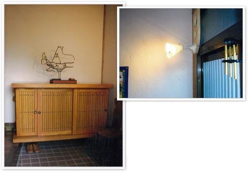 玄関ドア上に設置した照明で、しっくい塗り壁の模様やげた箱上のオブジェのシルエットを楽しむことができます。>