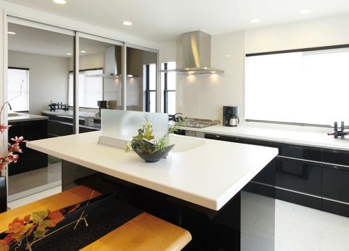システムキッチンは黒、という奥さまのイメージにピッタリだったのはサンウェーブの「魅せるキッチン」サンヴァリエ<ピット>。 リビングに美しく調和する意匠性の高い対面キッチンは食品庫の鏡面扉の効果と相まって明るく広い空間を演出しています。>